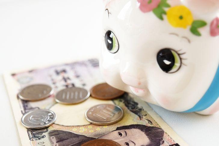 お金と貯金箱の写真